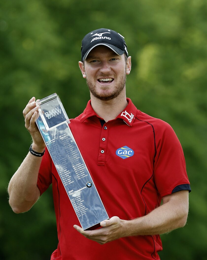 England's Chris Wood holds the trophy after winning the PGA Championship at Wentworth Club, in Virginia Water, England, Sunday May 29, 2016.  Wood shot a front-nine 29 before overcoming a late run of bogeys to win the PGA Championship by one stroke for the biggest victory of his career on Sunday. (