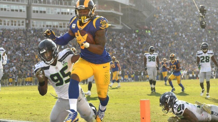 Rams running back Todd Gurley scores a touchdown in front of Seattle Seahawks defensive end Dion Jordan in the second quarter at the Coliseum on Sunday.