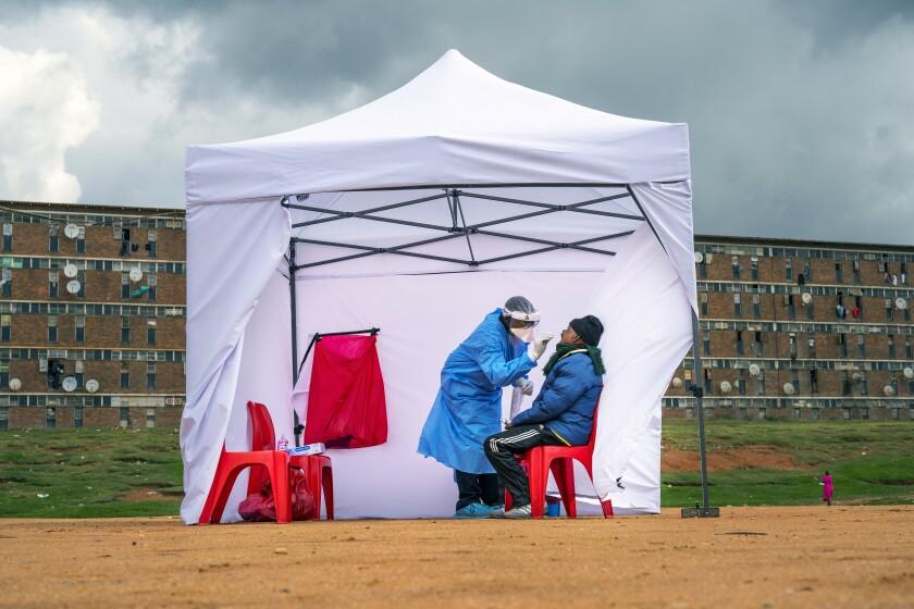یک مرد در حال آزمایش COVID-19 در یک چادر است