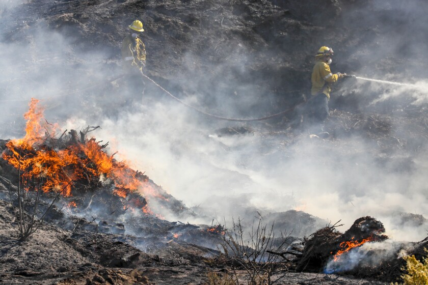 Firefighters battle the Tick fire along Sierra Highway on Friday in Santa Clarita.