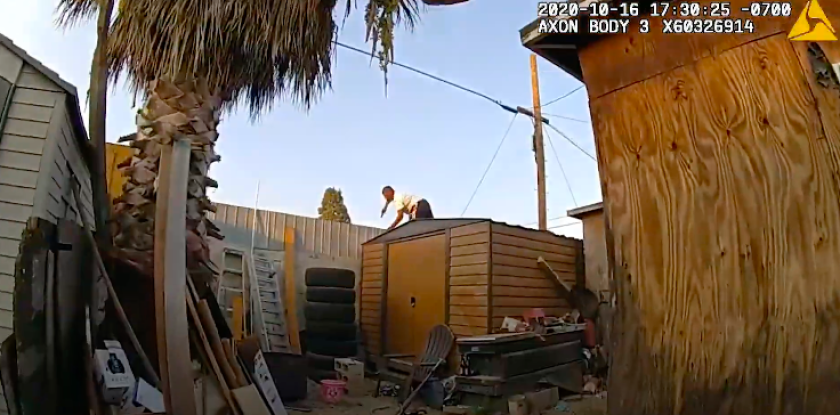 Screen grab from body camera video shows a man jumping over a backyard fence