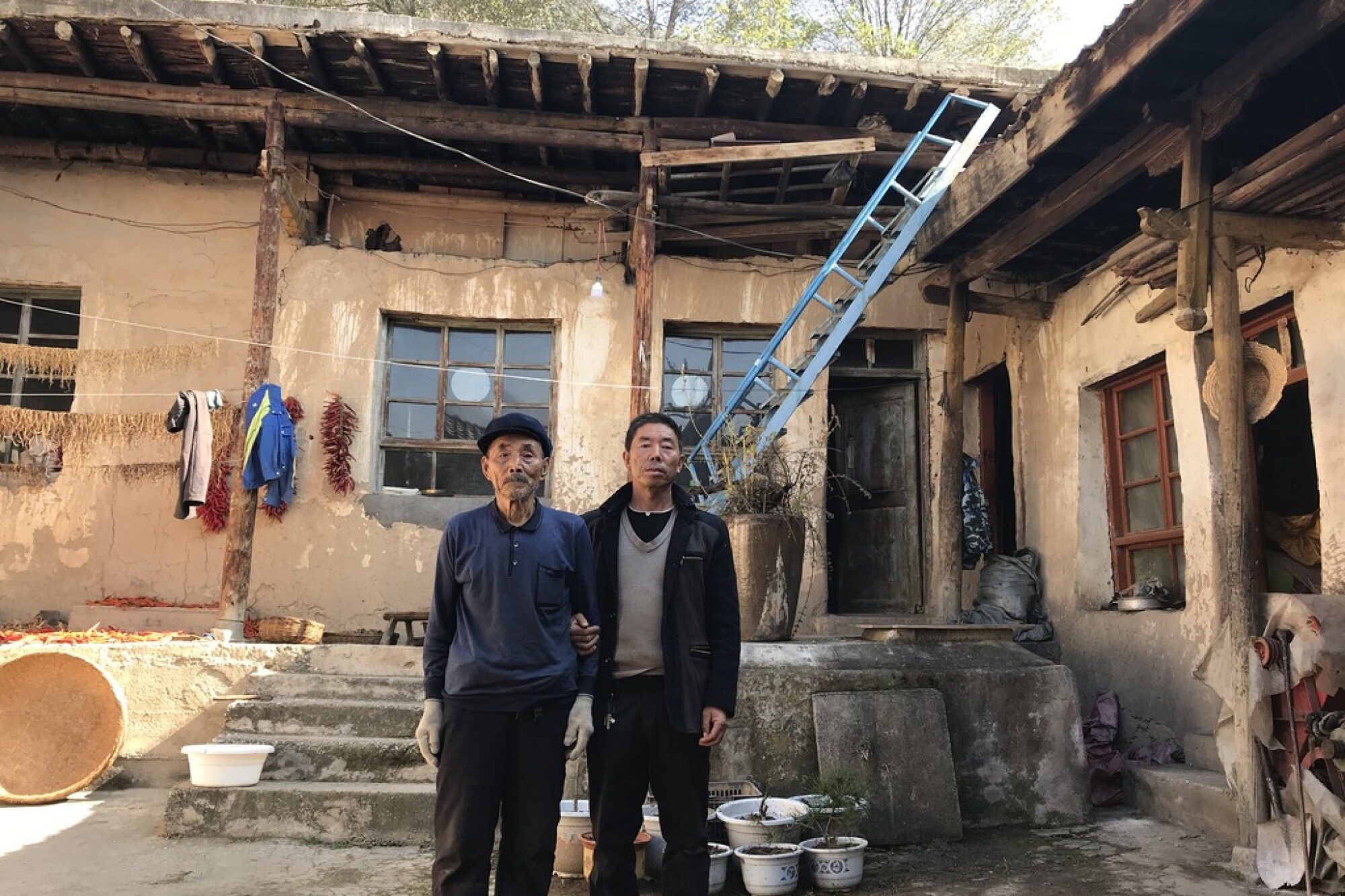 Yang Qinglai and his son Yang Jiacun are among a handful of residents still living in Lianghekou, China