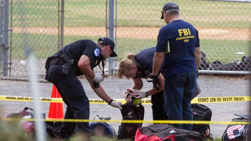 An FBI Evidence Response team inspects the contents of one of the many bags left at the scene of a s