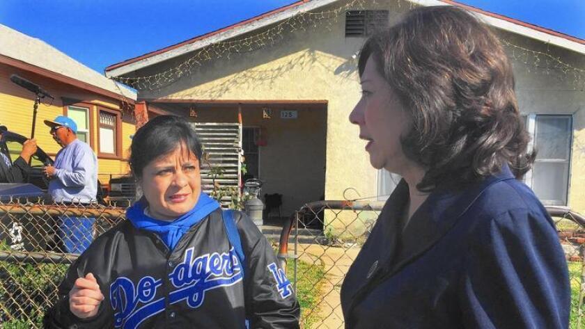 Amelia Vallejo habla con la supervisora del condado de Los Ángeles, Hilda Solís, acerca de la contaminación por plomo hallada en su jardín.