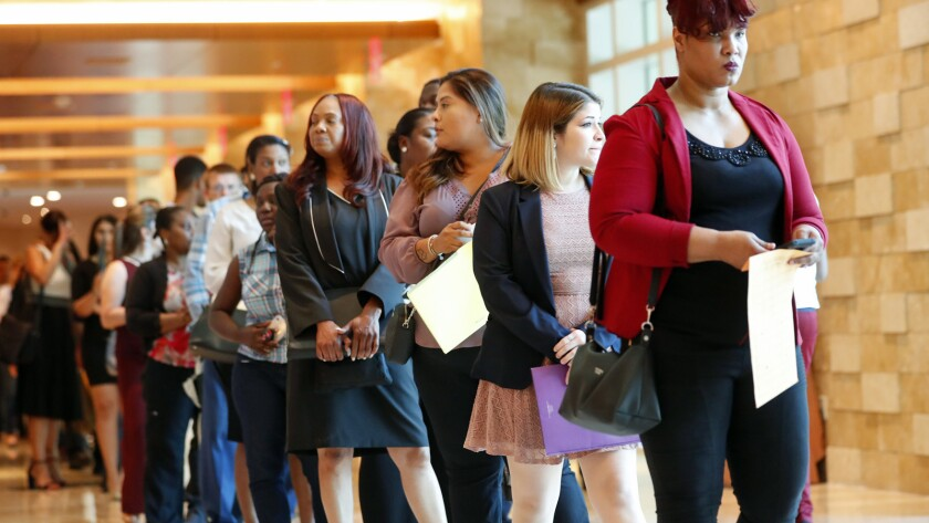 In this Tuesday, June 4, 2019 photo, job applicants line up at the Seminole Hard Rock Hotel & Casino