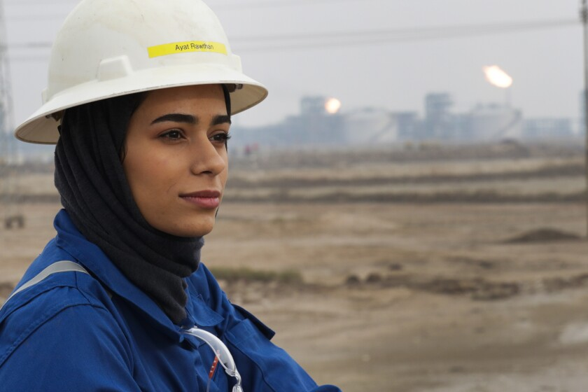 Ayat Rawthan, a petrochemical engineer, poses for a photo near an oil field outside Basra, Iraq, Tuesday, Feb. 5, 2021. Rawthan is among just a handful of women who have eschewed the dreary office jobs typically handed to female petrochemical engineers in Iraq. Instead, they chose to become trailblazers in the country's oil industry, taking up the grueling work of drilling. (AP Photo/Nabil al-Jourani)