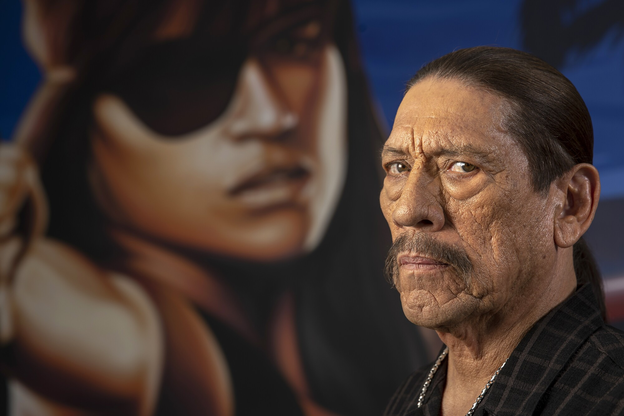 Danny Trejo in front of an image of a person with a black eye patch