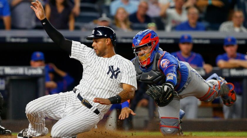 New York Yankees' Aaron Hicks (31) beats the tag from New York Mets' Rene Rivera (44) to score a run in the fourth inning at Yankee Stadium on Aug. 14, 2017.