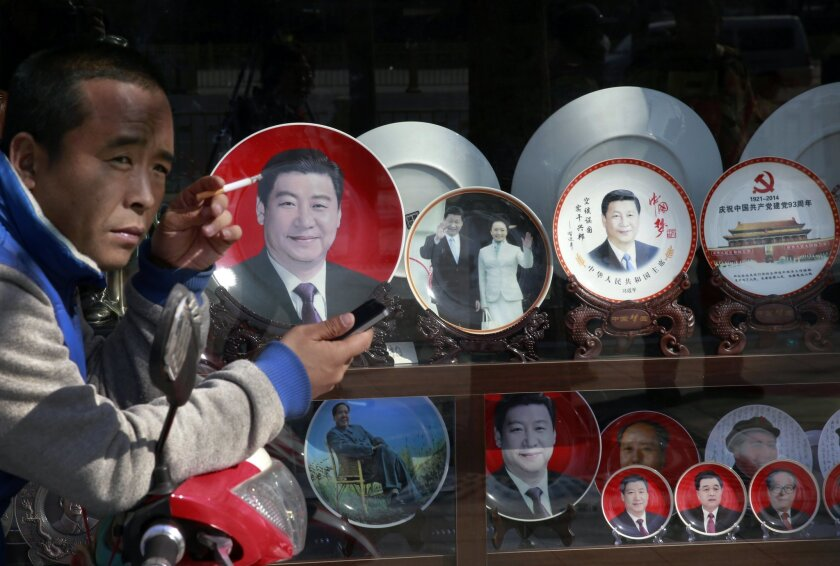 In this March 4, 2015 photo, a man smokes near the souvenir plates bearing images of Chinese President Xi Jinping on display together with China's former presidents at a shop near Tiananmen Square in Beijing. Barely two years into office, Xi has attracted an extraordinary degree of attention to his