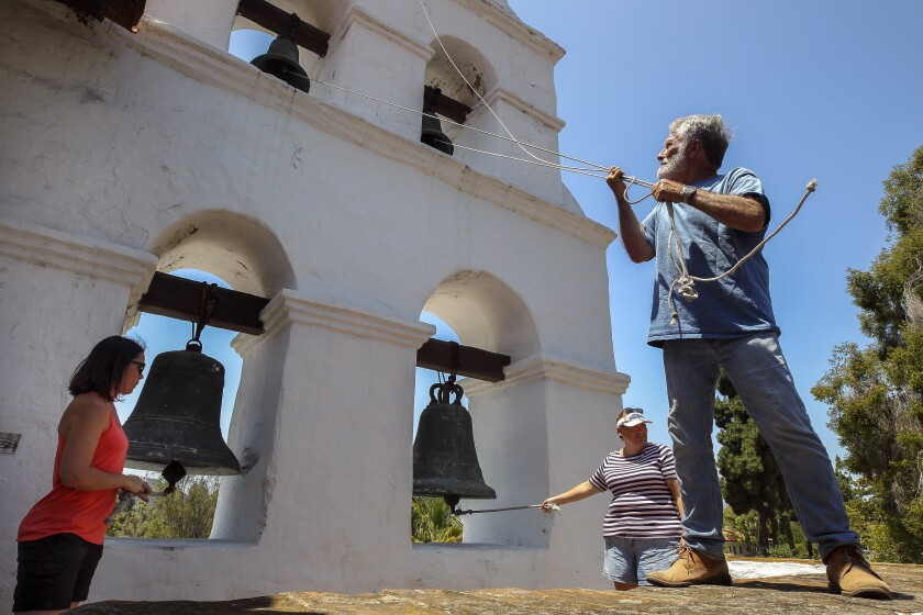 George Lane, right, Crystal Carr, left, and Misty Suposs pull the ropes to ring all five bells at the same time, which is only done once a year, during the annual Festival of the Bells at Mission Basilica San Diego de Alcalá on Saturday.