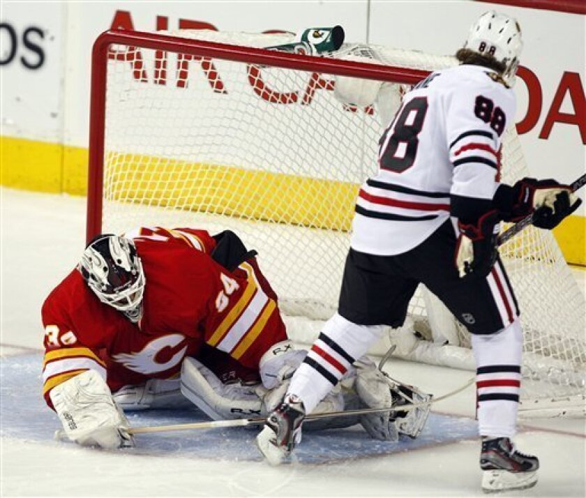 Chicago Blackhawks' Patrick Kane, right, scores the winning goal on Calgary Flames goalie Miikka Kiprusoff, from Finland, during overtime of an NHL hockey game in Calgary, Alberta, Saturday, Feb. 2, 2013. The Blackhawks defeated the Flames 3-2 in a shootout. (AP Photo/The Canadian Press, Jeff McInt