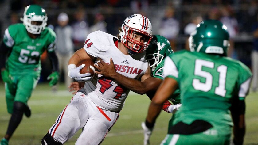 Christian running back Joey Morones, who had five rushing touchdowns, tries to elude a Lincoln tackler.