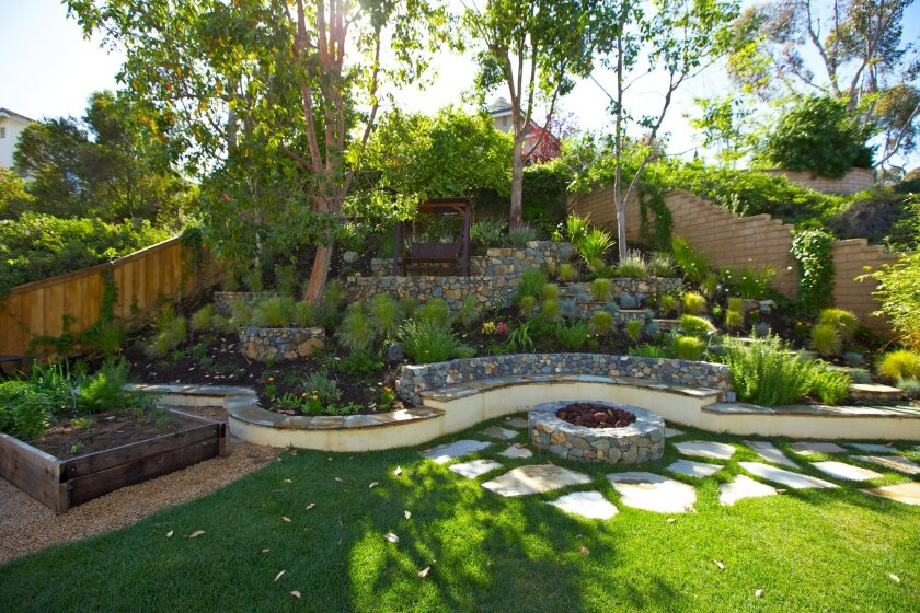 Backyard Vacations won the top award for small projects for a design that transformed a barren slope into a stepped design with cobblestones, a walkway and an area for a swinging bench.