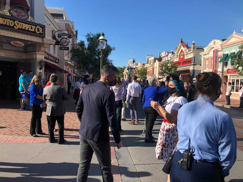 Disneyland workers line the park's Main Street USA to greet guests