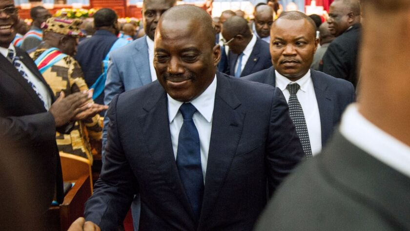 Congolese President Joseph Kabila (C) shakes hands during a special joint session of parliament the