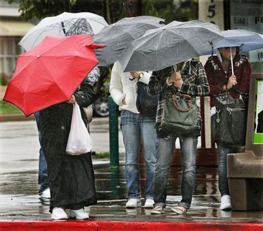 Well-prepared San Diegans waited in the rain yesterday at a Pacific Beach bus stop. (Howard Lipin / Union-Tribune)