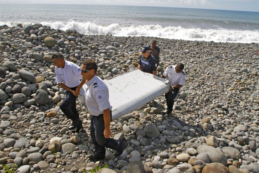 """FILE - In this July 29, 2015, file photo, French police officers carry a piece of debris from a plane known as a """"flaperon"""" on the shore iof Saint-Andre, Reunion Island. Three new pieces of debris found washed ashore in Mozambique and the Indian Ocean island of Mauritius will be examined by investi"""
