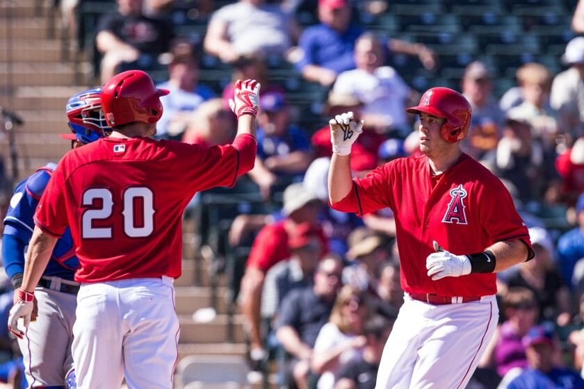 Angels outfielder Matt Joyce greets teammate C.J. Cron after Cron hit a home run in a spring training exhibition.