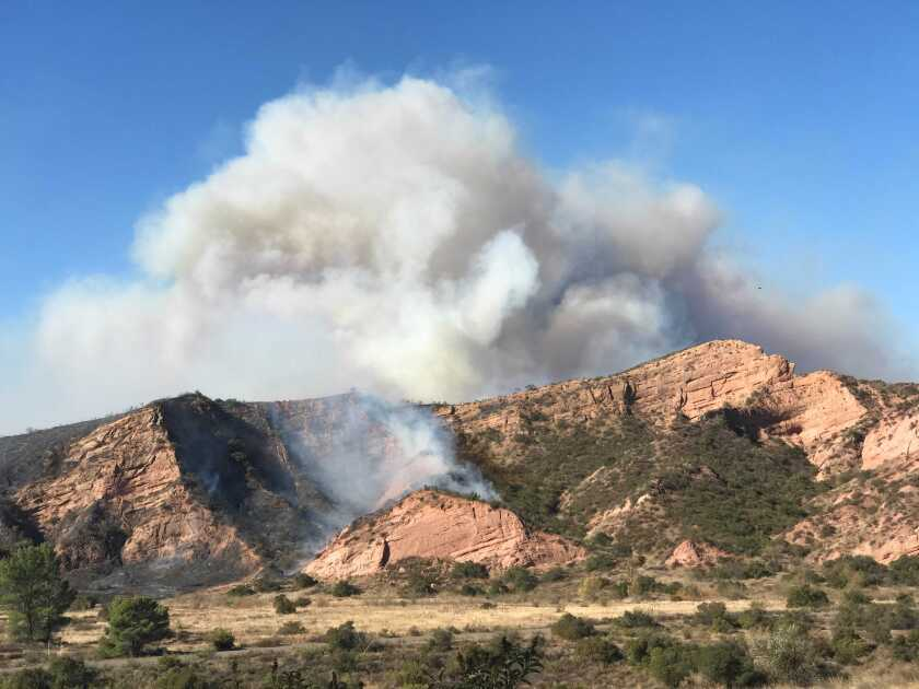 A large plume of smoke from the Bond fire rises in the hills above Santiago Canyon Road