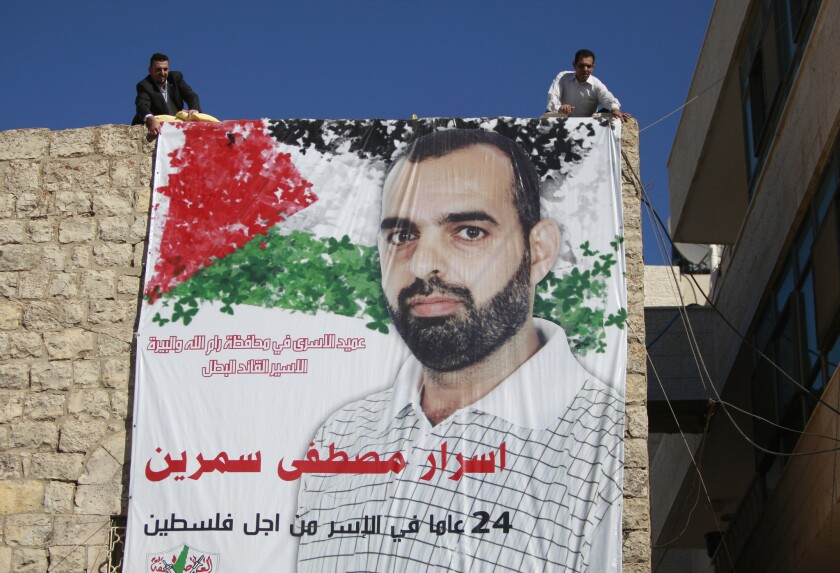 """Palestinian relatives of prisoner Israr Samreen, who has been jailed by Israel, hang a poster that reads, """"leader of prisoners in Ramallah, the heroic prisoner, Israr Mostafa Samreen, 24-year prisoner for Palestine."""" Samreen is expected to be among the prisoners released by Israel this week."""
