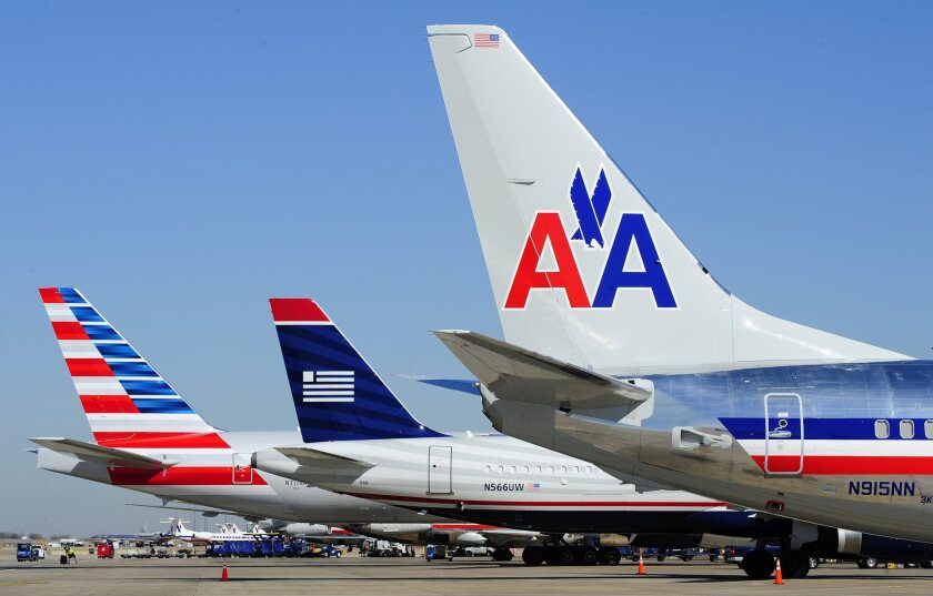 US Airways and American Airlines jets are parked side by side at Dallas/Fort Worth International Airport in 2013. The merger between the two airlines takes a big step Oct. 17, by which time American's reservation systems should take over all flight bookings for the combined carrier.