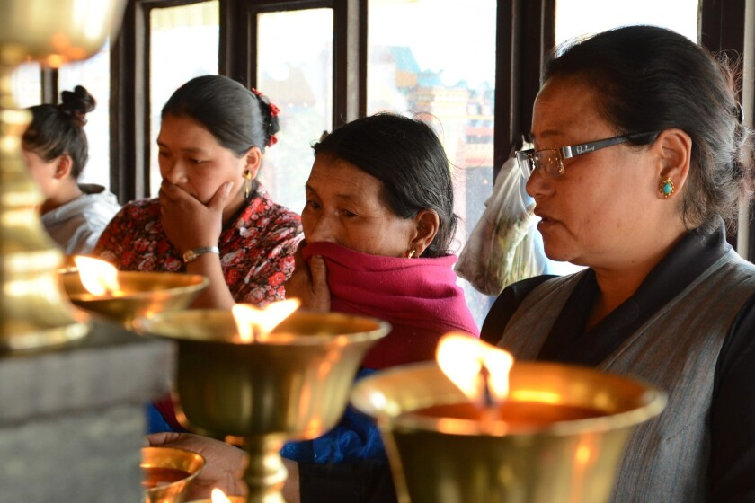 The mother of Phurtemba Sherpa (second from the right), a victim of the Everest avalanche, and family members light oil lamps Sunday as they perform rituals at the Sherpa Monastery in Katmandu.