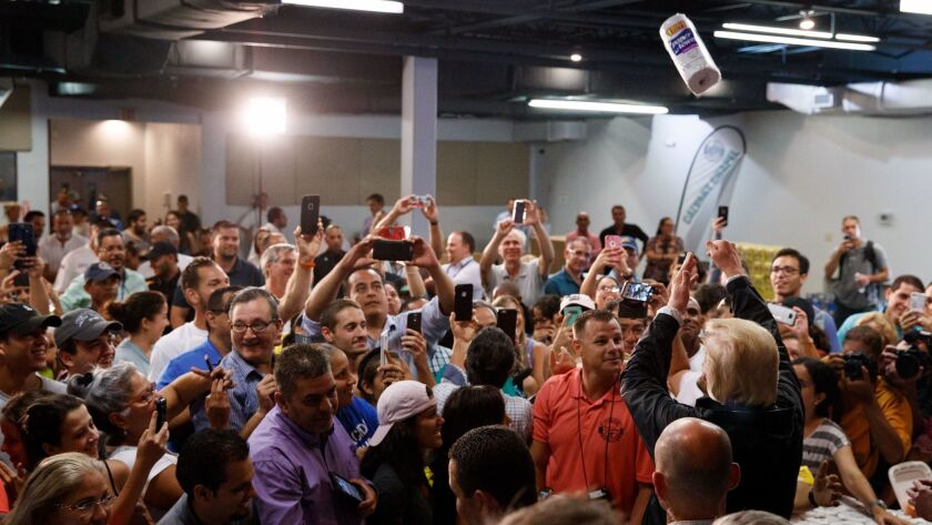 President Trump tosses paper towels into a crowd at Calvary Chapel in Guaynabo, Puerto Rico, on Oct. 3.