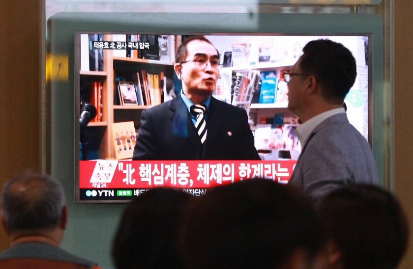 """En esta foto de archivo, 17 de agosto de 2016, gente mira un noticioso de TV con la imagen del diplomático norcoreano Thae Yong Ho, en Seúl, Corea del Sur. Corea del Norte calificó el sábado 20 de agosto de 2016 de criminal y """"escoria humana"""" a Thae, un diplomático jerárquico en Londres, que desertó recientemente a Corea del Sur, en su primera reacción oficial al suceso. La leyenda dice, """"Diplomático norcoreano de alta jerarquía"""". (AP Foto/Ahn Young-joon. File)"""