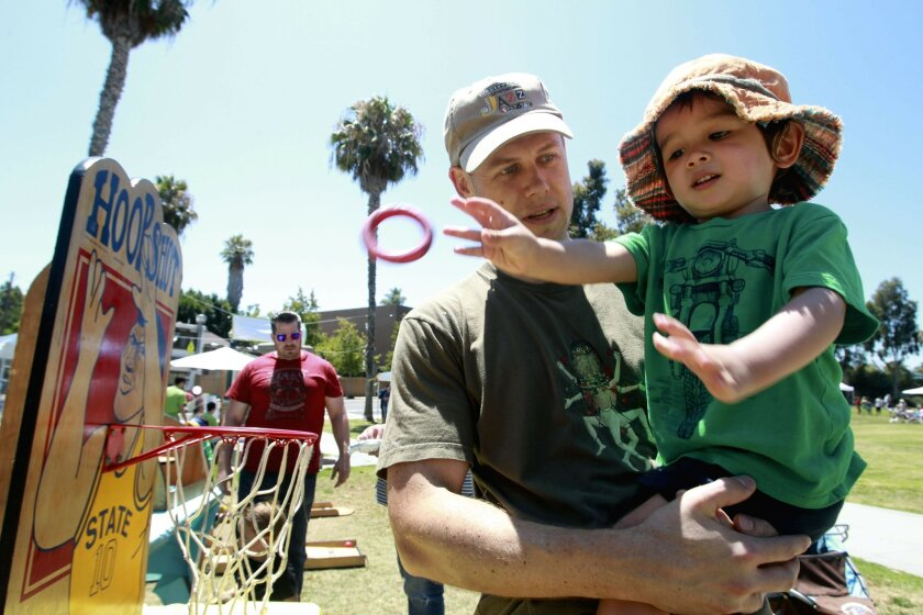 Two-year-old Felix Idell tosses a ring as he plays various games while being held by his dad matt Idell  during the celebration of the 125th birthday of University Heights, called UH 125 Day, at Trolley Barn Park in University Heights on Saturday.