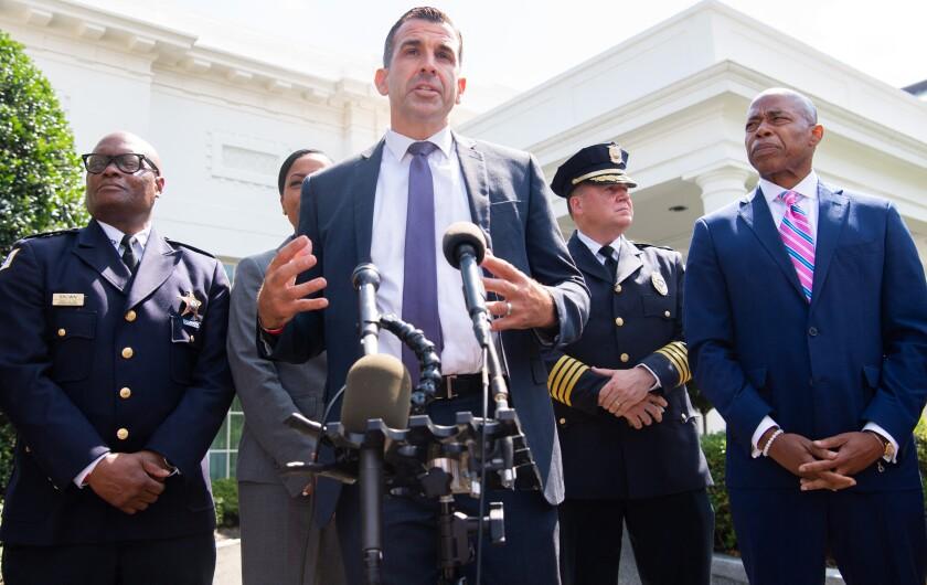 Mayor Sam Liccardo of San Jose speaks at microphones while people stand behind him
