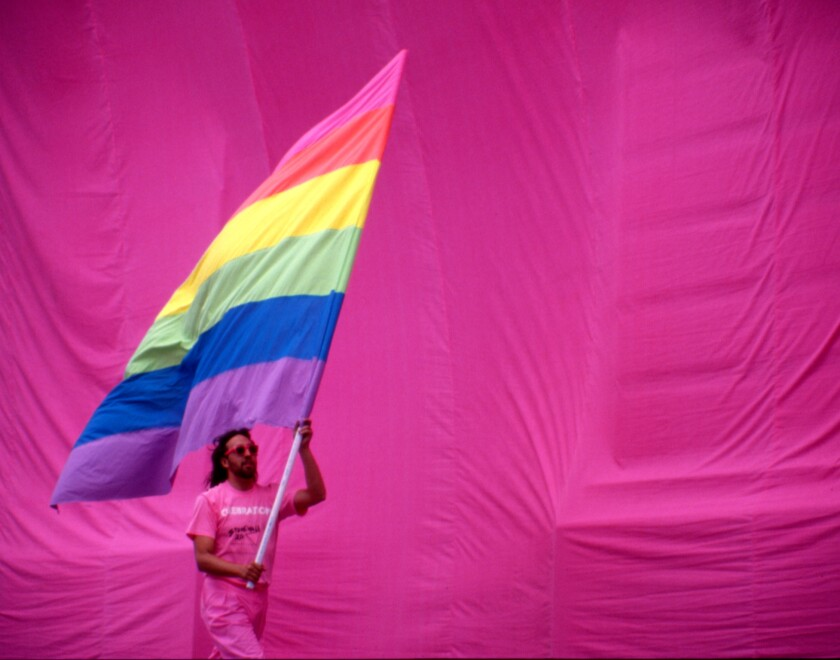 Gilbert Baker holds the rainbow flag against a pink backdrop