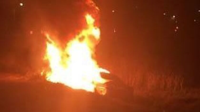 A deputy carried a woman from this car before flames engulfed it.