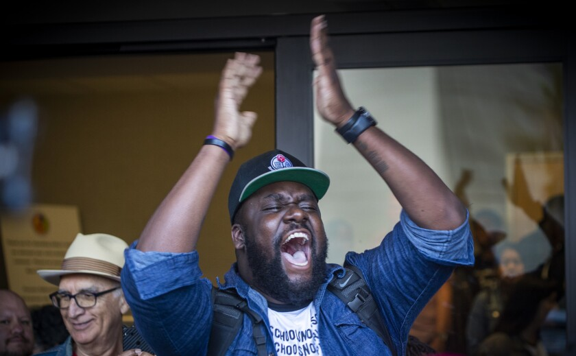 David Turner, center, of Brothers, Sons, Selves LA celebrates after the L.A. school board voted to end the controversial policy of interrupting classes to randomly search students.