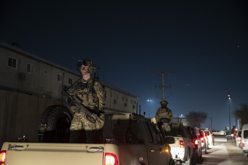 Armed soldiers stand guard in Afghanistan.