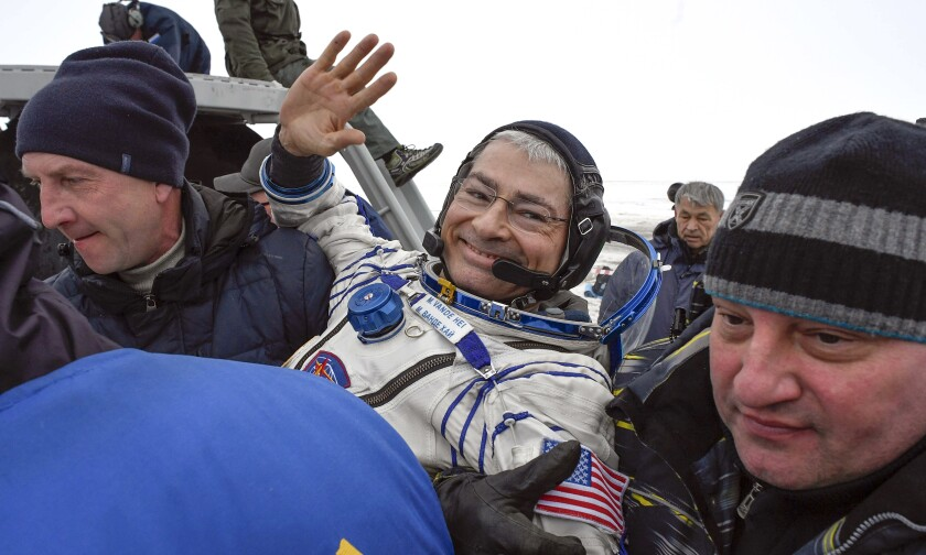 FILE - In this Feb. 28, 2018 file photo, ground personnel carry NASA astronaut Mark Vande Hei after the landing of the Soyuz MS-06 space capsule in a remote area south-east of the Kazakh town of Zhezkazgan, Kazakhstan. Vande Hei learned last week that he'll launch April 9, 2021, on a Russian rocket to the International Space Station.Vande Hei said Monday, March 15 he may have to give up his return Soyuz seat in the fall to a Russian movie-making tourist. If that happens, he'll have to wait for the next Soyuz ride home in spring 2022. (Alexander Nemenov/Pool Photo via AP, File)