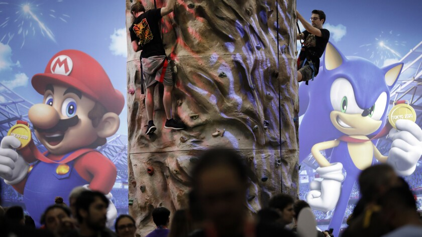 "LOS ANGELES, CA -- JUNE 11, 2019: Guests climb a wall at Nintendo's ""Mario and Sonic at the Olympic"