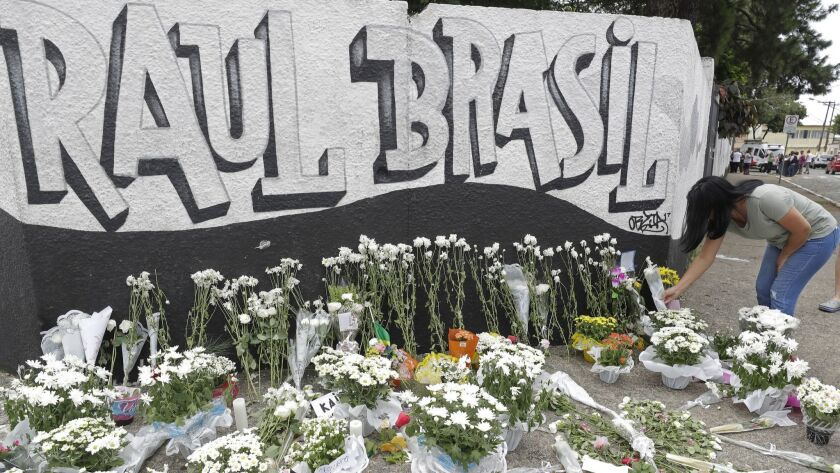 A woman leaves flowers one day after a mass, school shooting outside the Raul Brasil state school i