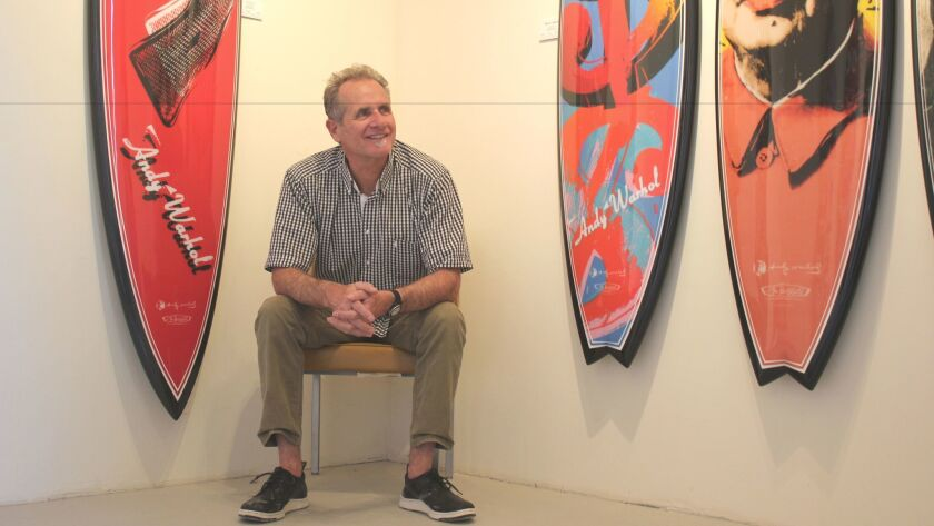 Surfboard shaper and artist Tim Bessell poses with some of his Andy Warhol-inspired creations.