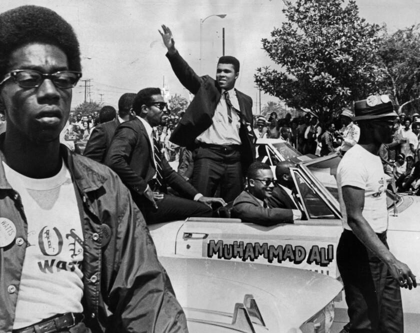 Muhammad Ali, grand marshal of a parade ending 1967's Watts Summer Festival, waves at spectators.