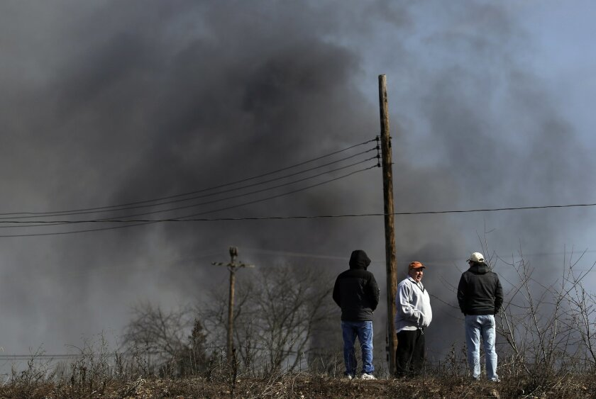 John Adams, left, Tommy DeStefano, center, and Dave Ellmer converse as they stand on a hill overlooking a large warehouse fire a day after flames engulfed the facility, Friday, Feb. 12, 2016, in Hillsborough, N.J. Firefighters have contained the massive  fire and officials said the blaze didn't pos