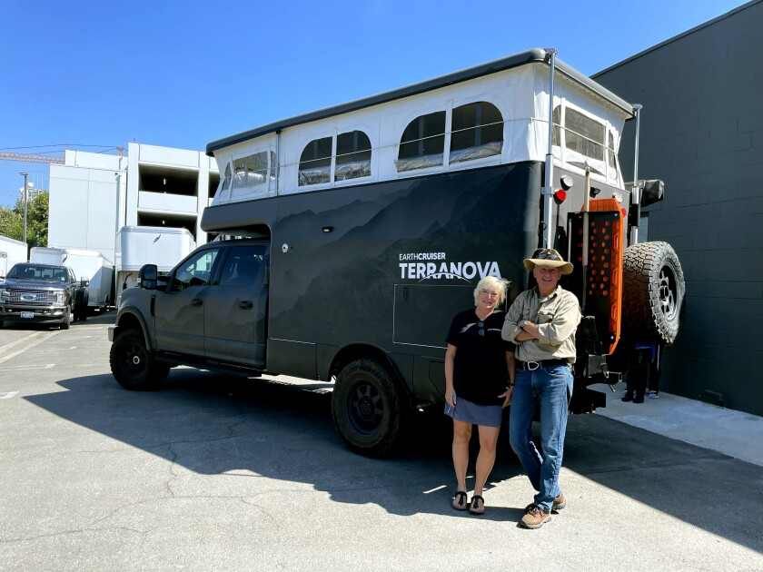 EarthCruiser founders Michelle Boltz and Lance Gillies next to an overland expedition vehicle.