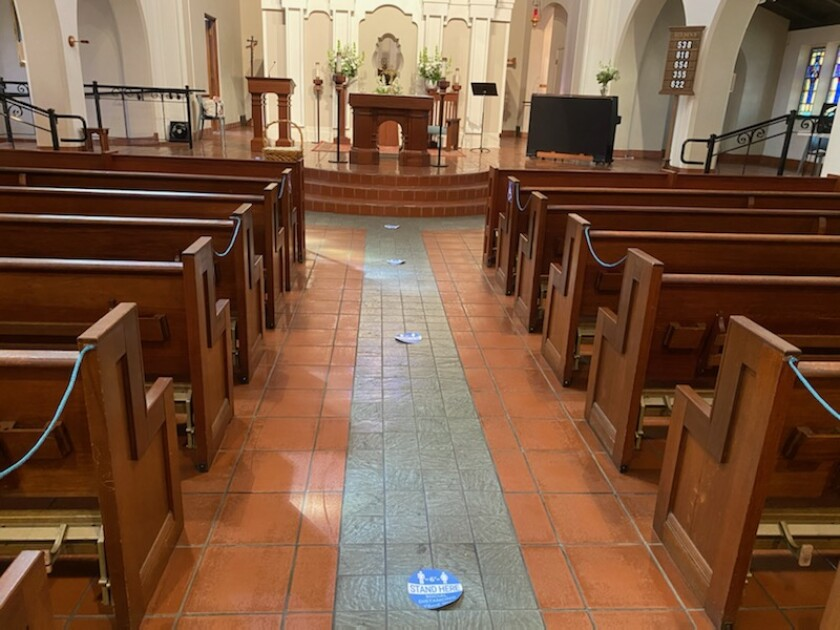 Sacred Heart Church of Ocean Beach has pews roped off and placement mats on the floor to keep guests at a safe distance.
