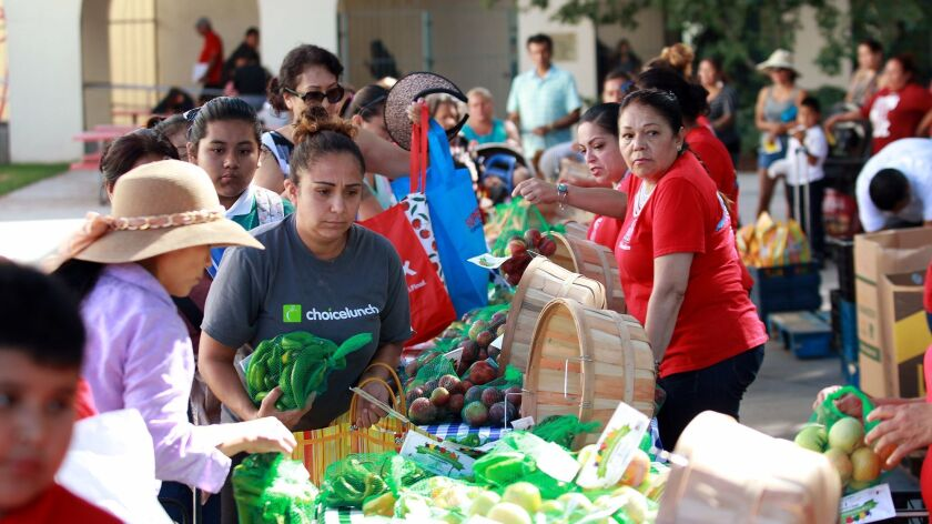 Familys collect food from the Second Harvest Food Bank of Orange County's farmers market at Santa An