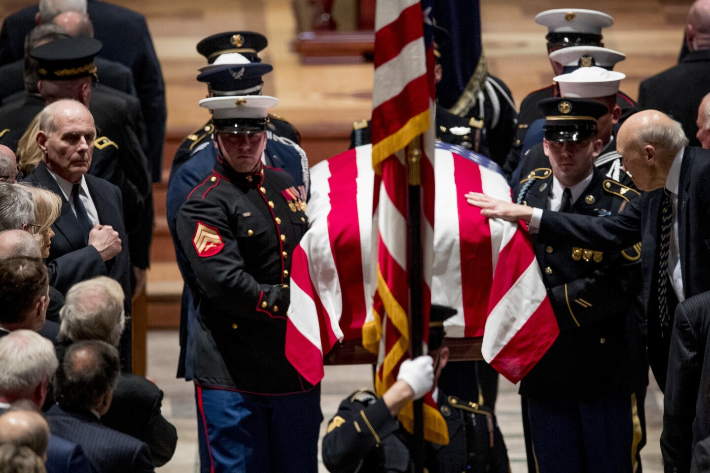 President Donald Trump's Chief of Staff John Kelly, left, watches as Former Sen. Alan Simpson, R-Wyo, right, touches the flag-draped casket of former President George H.W. Bush as it is carried out by a military honor guard during a State Funeral at the National Cathedral.