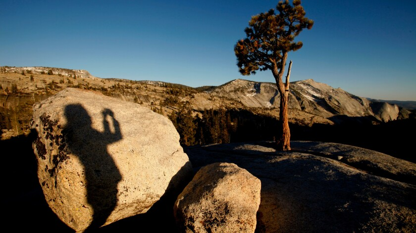 The shadow of a photographer is cast on a boulder at Olmsted Point in the high country off Tioga Road in Yosemite National Park.