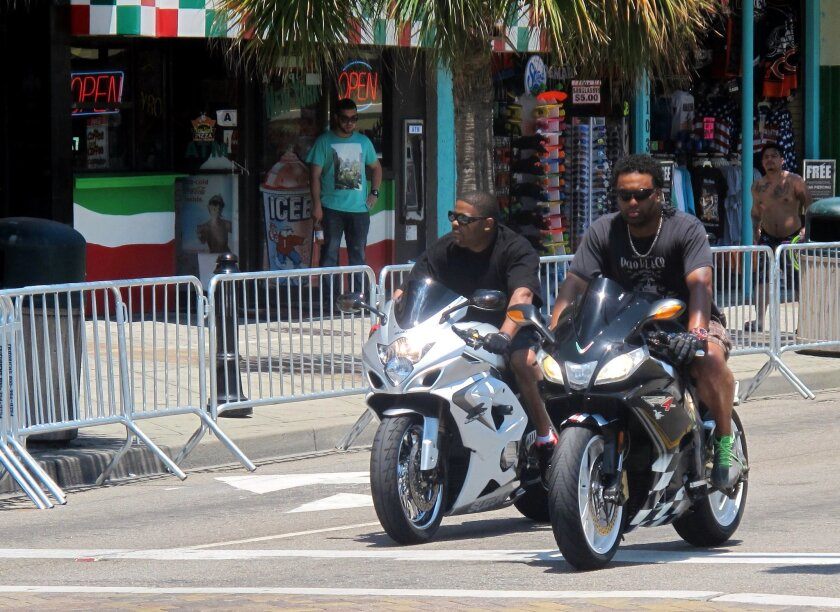 In this photo taken Tuesday, May 19, 2015, motorcyclists ride through Myrtle Beach, S.C. Tens of thousands of bilkers are expected in the area this Memorial Day weekend for the annual Atlantic Beach Bikefest that begins in the predominantly black hamlet of Atlantic Beach on Friday, May 22. After violence in nearby communities left three dead last year, visitors will be greeted with increased security measures. (AP Photo/Bruce Smith)