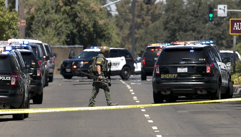 Law enforcement officers, including this Sacramento County sheriff's deputy surround a hotel where s