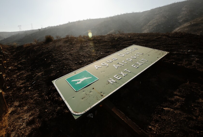 A sign for Agua Dulce Airport lies next to the 14 Freeway near the scene of the Soledad fire.