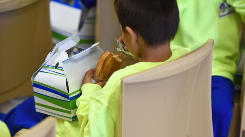 A migrant boy eats at South Texas Family Residential Center in Dilley, Texas on Aug. 9.
