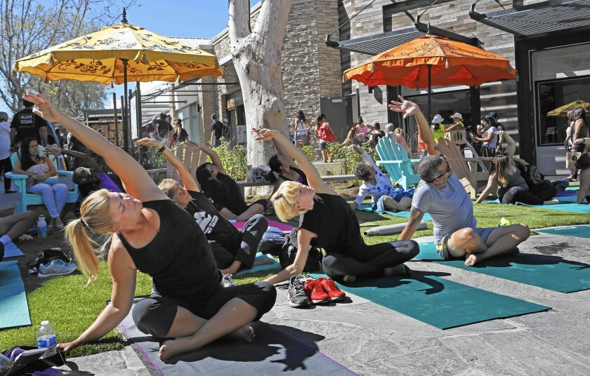 "Yogaworks conducts a free outdoor yoga class Friday at the Village at Westfield Topanga.  ""It's pedestrian friendly, dog friendly, family friendly. It's going to create a vitality in the region that we haven't seen before."" Councilman Bob Blumenfield said."